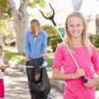 Mother And Daughters Picking Up Litter In Suburban Street - Stockfoto