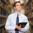 Manager In Warehouse With Clipboard - Lizenzfreies Foto