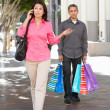 Fed Up Man Carrying Partners Shopping Bags On City Street — Stock Photo