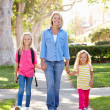 Mother And Daughters Walking To School On Suburban Street — Stock Photo #25049863
