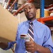 Businessman Scanning Package In Warehouse — Stock Photo