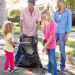 Family Picking Up Litter In Suburban Street - Stock Photo