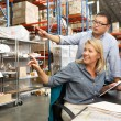 Stock Photo: Business Colleagues Working At Desk In Warehouse