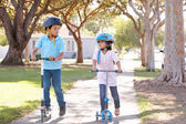 Boy And Girl Wearing Safety Helmets And Riding Scooters — Stockfoto