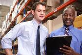 Dos empresarios con portapapeles en almacén — Foto de Stock