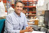Podnikatel pracuje u stolu ve skladu — Stock fotografie