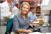 Empresaria trabajando en recepción en almacén — Foto de Stock