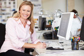 Woman Working At Desk In Busy Creative Office — Stock Photo