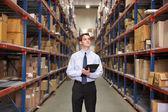 Manager in magazijn met klembord — Stockfoto