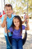 Boy And Girl Playing On Swing In Park — Stok fotoğraf