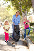 Mother And Daughters Picking Up Litter In Suburban Street — Stockfoto