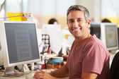 Man Working At Desk In Busy Creative Office — Stock Photo