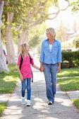 母と娘の郊外の通りに学校に歩いて — ストック写真