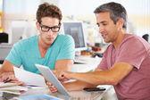 Deux hommes à l'aide de la tablette tactile au bureau créatif — Photo