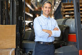 Portrait Of Man With Fork Lift Truck In Warehouse — Stock Photo