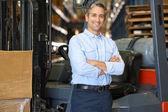 Portret van man met fork lift truck in magazijn — Stockfoto