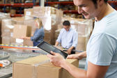 Tablet bilgisayar kullanarak dağıtım depo işçisi — Stok fotoğraf