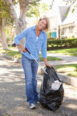Woman Picking Up Litter In Suburban Street — Stock Photo