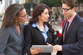 Businessman And Businesswomen Using Digital Tablet Outside — Stock Photo