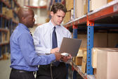 Two Businessmen With Laptop In Warehouse — Stock Photo