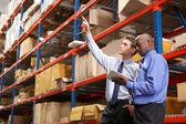 Twee zakenlieden met digitale tablet in magazijn — Stockfoto
