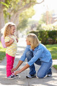 Mother Helping Daughter Tie Shoe Laces On Walk To School — Stock Photo