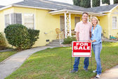 Couple Standing By For Sale Sign Outside Home — Stock Photo