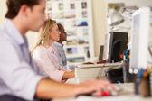 Travailleurs aux comptoirs dans bureau créatif occupé — Photo