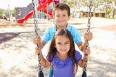 мальчик и девочка, играя на качелях в парке — Стоковое фото