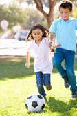 Dvě děti spolu hráli fotbal — Stock fotografie