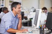 Hombre que trabajaba en el despacho de ocupado creativa — Foto de Stock