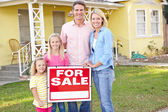 Family Standing By For Sale Sign Outside Home — Stock Photo