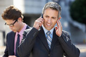 Businessman Speaking On Mobile Phone In Noisy Surroundings — Stock Photo