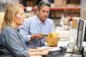 Business Colleagues Working At Desk In Warehouse — Stockfoto