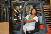 Woman Driving Fork Lift Truck In Warehouse — Stock Photo