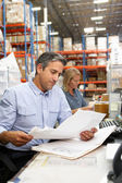 Collega's werken aan balie in magazijn — Stockfoto