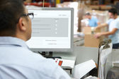 Person At Computer Terminal In Distribution Warehouse — Foto Stock