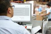 Persoon achter computer terminal in distributie magazijn — Stockfoto
