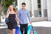 Fed Up Man Carrying Partners Shopping Bags On City Street — ストック写真