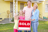 Family Standing By Sold Sign Outside Home — Stock Photo