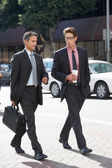 Two Businessman Chatting Whilst Crossing Street — Stock Photo