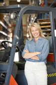 Portrait Of Woman With Fork Lift Truck In Warehouse — Stock Photo