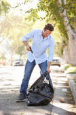 Man Picking Up Litter In Suburban Street — Foto Stock