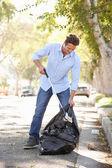 Uomo, raccogliendo i rifiuti in strada suburbana — Foto Stock
