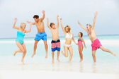 Multi Generation Family Having Fun In Sea On Beach Holiday — Foto de Stock