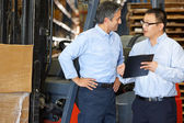 Businessmen Meeting By Fork Lift Truck In Warehouse — Stock Photo