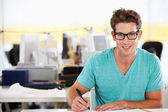 Man Writing At Desk In Busy Creative Office — Stock Photo