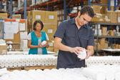 Ouvrier d'usine vérification des marchandises sur la ligne de production — Photo