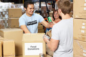 Volunteers Collecting Food Donations In Warehouse — Stock Photo
