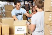 Vrijwilligers verzamelen voedsel donaties in magazijn — Stockfoto